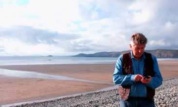 Man uses an app in a mobile phone on the beach.